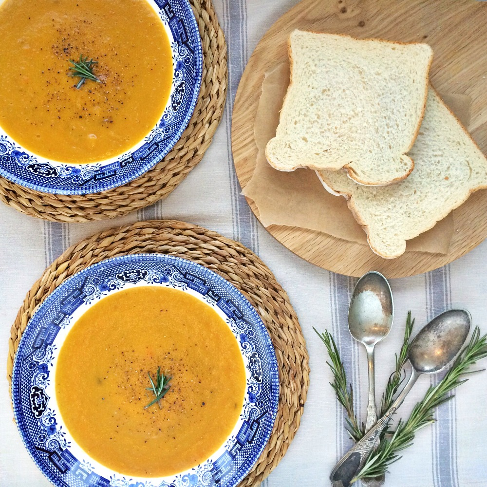 Two bowls of butternut squash soup in blue and white dishes, sitting on woven place mats. Next to the soup are 2 silver spoons with some sprigs of rosemary, and 2 slices of bread on brown paper on top of a wooden board.