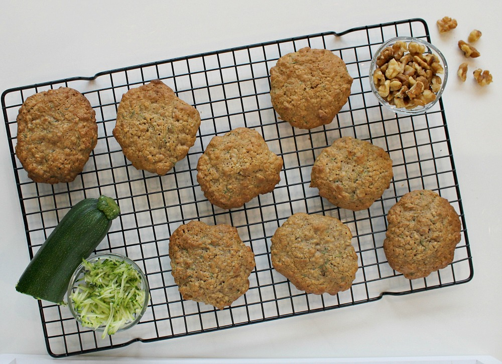 Oatmeal Courgette Cookies on a cooling rack with a little dish of walnuts and some courgette