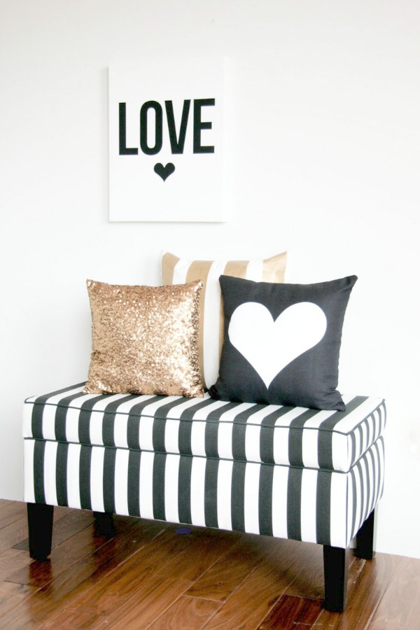 """A black and white striped upholstered bench, with 3 cushions on it in black, white and gold. A monochrome print with """"Love"""" written on it and a black heart hangs on the wall above the bench."""