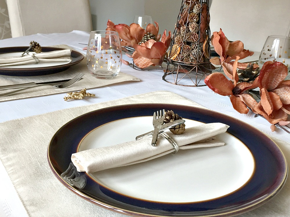 A table set for Thanksgiving dinner, with pinecones and flowers