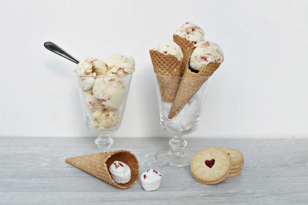 2 Glasses are on a table. One contains ice cream and a spoon, the other contains three ice cream cones filled with ice cream. In front is a cone with marshmallows in it and a stack of biscuits