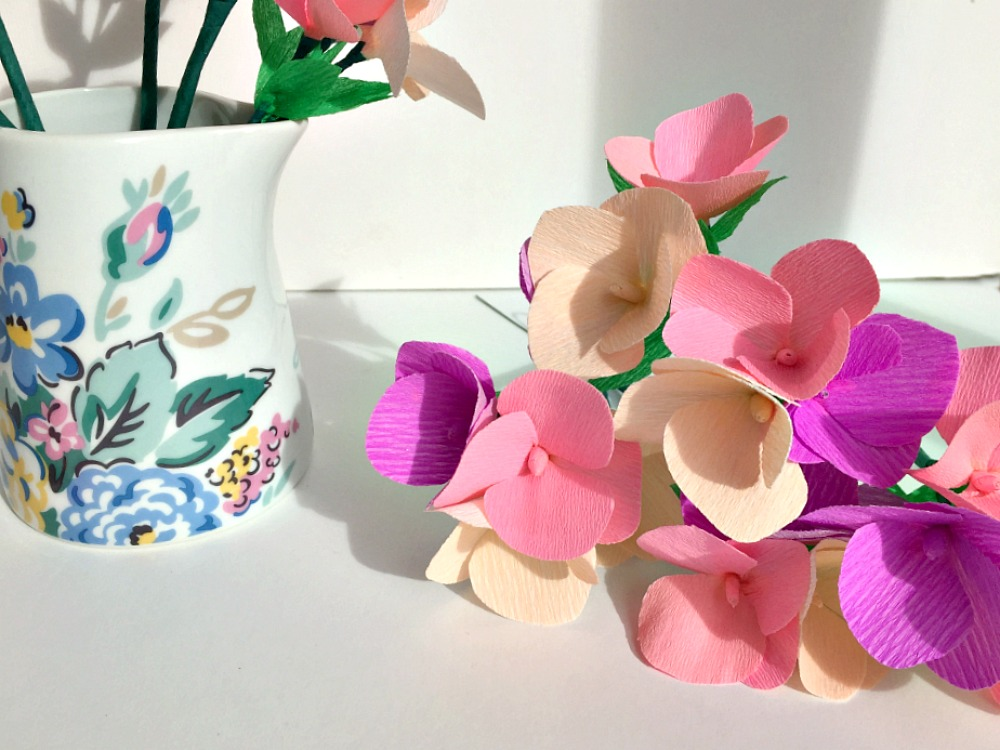 A bunch of paper flowers laid next to a jug with flowers on it
