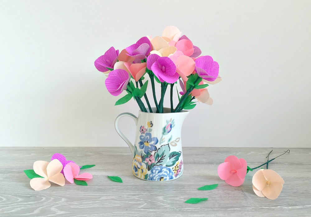 A jug with a bouquet of crepe paper flowers, with a few flowers around it