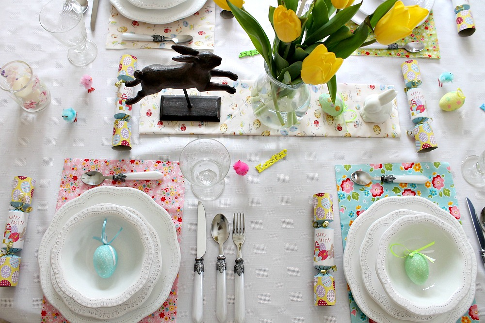 A table setting for Easter with eggs, Easter crackers, decorative eggs, tulips and little chicks