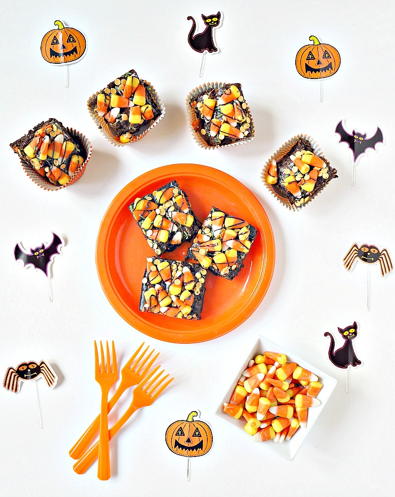 A plate of Halloween brownies surrounded by Halloween decorations and more candy corn brownies