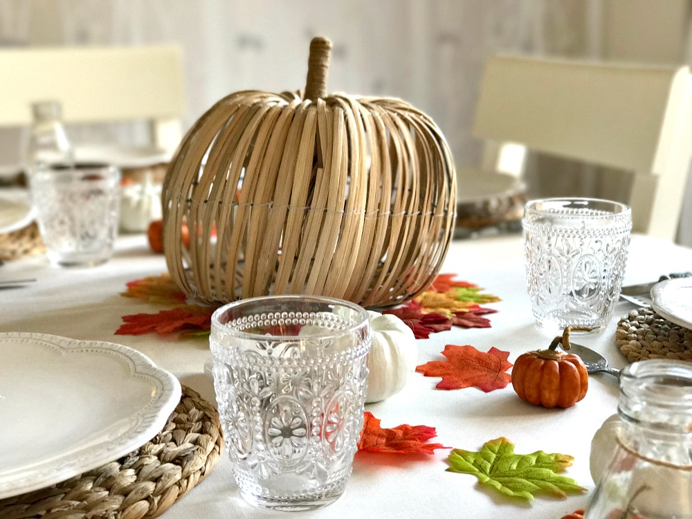 Thanksgiving table decorations, including a large wicker pumpkin and smaller fake pumpkins and leaves, set for a festive meal.