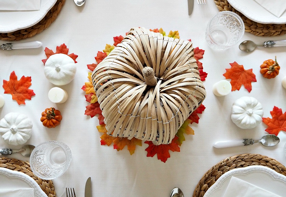 A large wicker pumpkin set on a table as part of Thanksgiving decorations