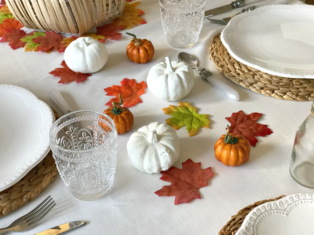 A Thanksgiving tablescape with white and orange pumpkins, fake leaves, crockery and cutlery.