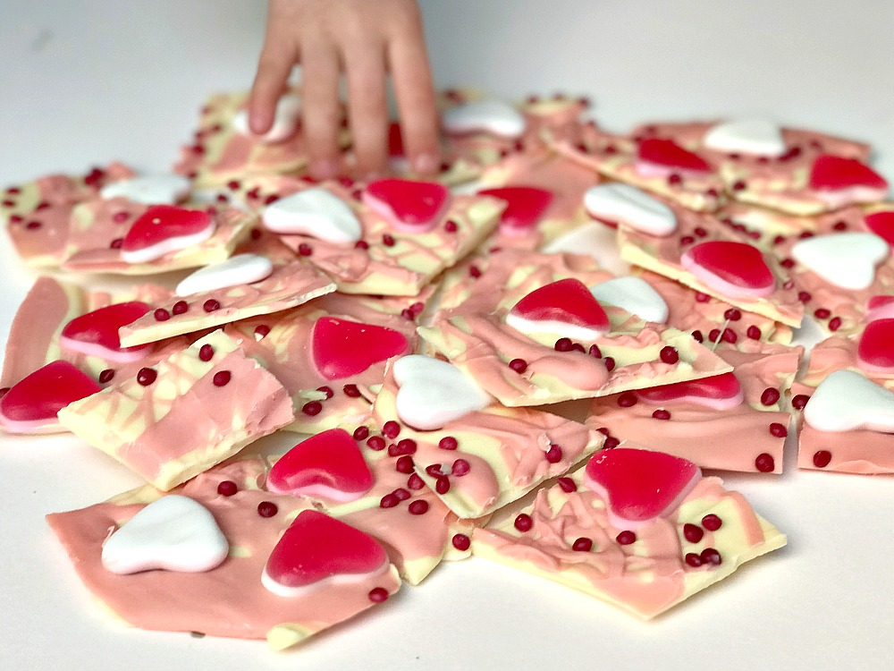 A Valentine's Day treat of chocolate bark. White and pink chocolate covered in pink hearts and sprinkles