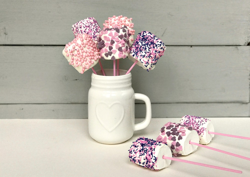 A white vase or mug with 5 marshmallow pops in it. They are on pink lolly sticks and covered with pink and purple hearts and sprinkles. Next to the base is 3 further marshmallow pops.