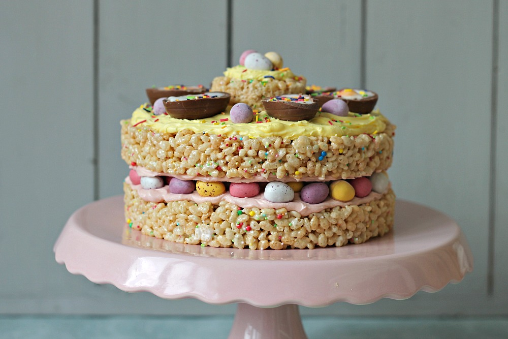 An Easter cake make out of rice crispy treats sits on a pink cake stand.