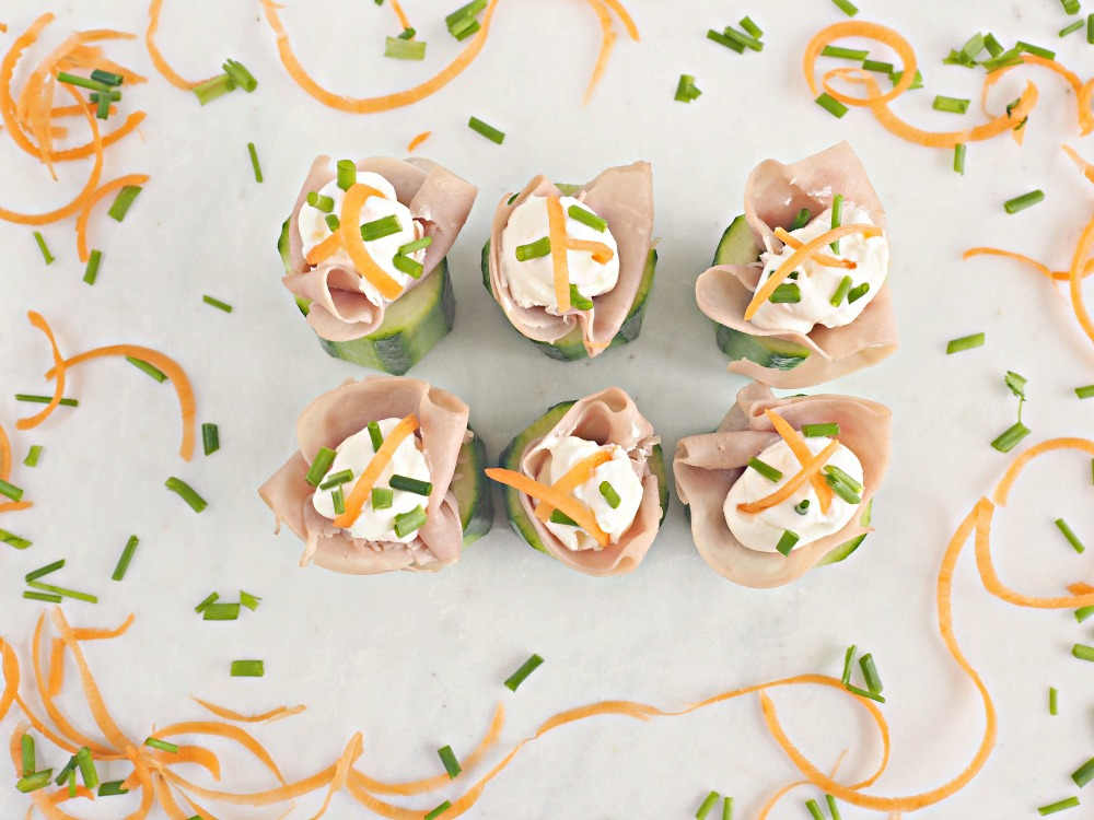 A top down view on some ham and cucumber bites, stuffed with cream cheese and topped with shredded carrot and chives