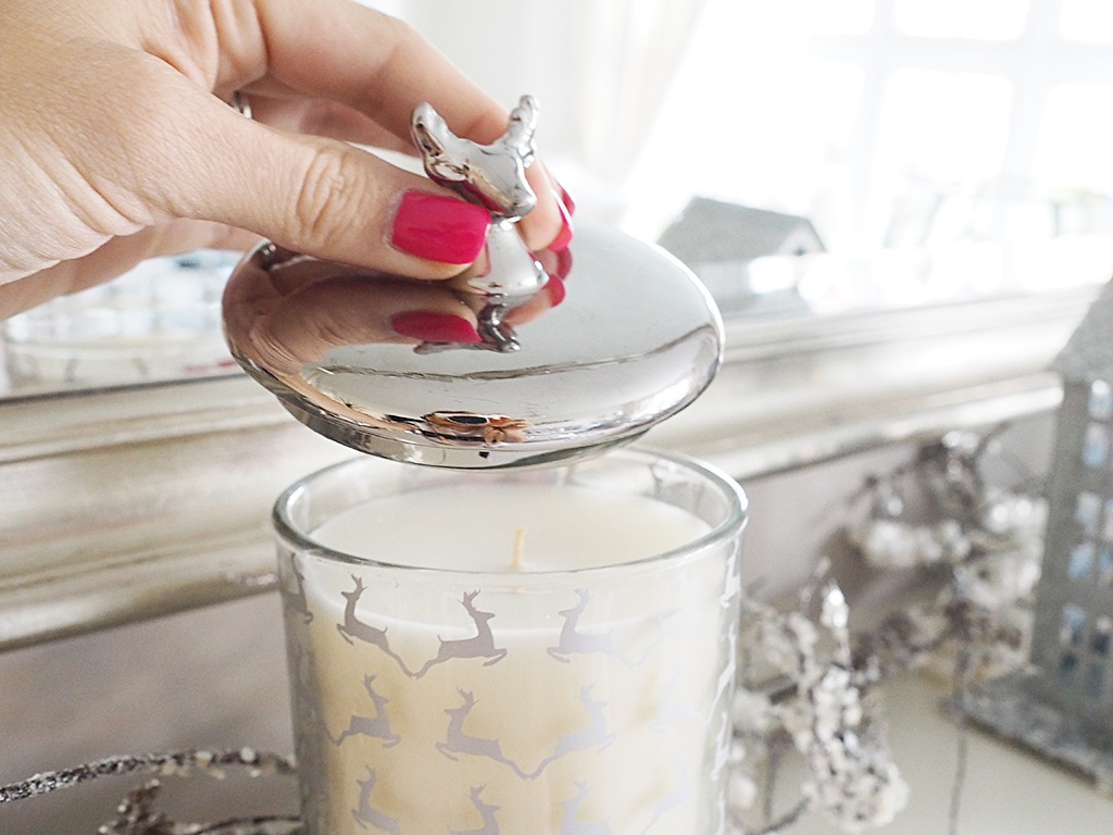 A candle with reindeer on the glass and a reindeer head on the lid