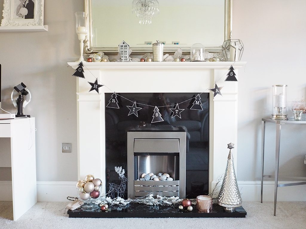 Decorating a Christmas Fireplace A fireplace decorated for Christmas with silver and rose gold accents for a modern look