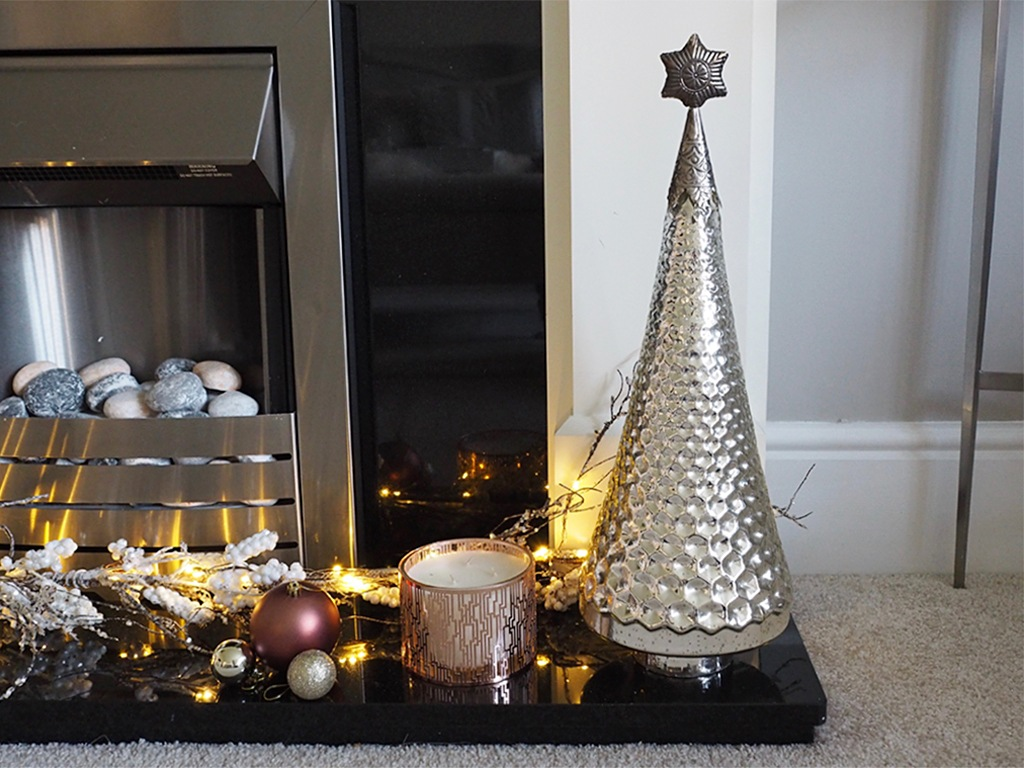 A fireplace with Christmas decorations lit up on it