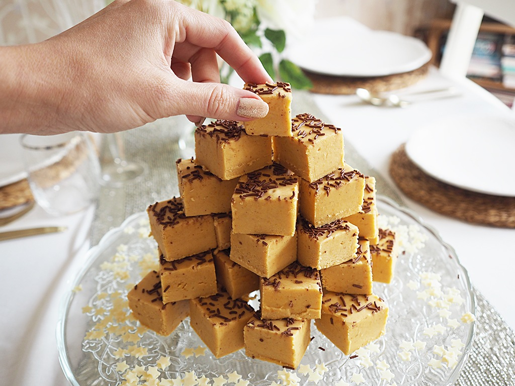 A hand taking a piece of pumpkin fudge from the top of a big pile.