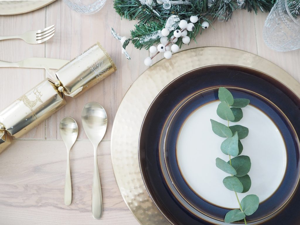 A table place setting for Christmas. A gold charger with blue white and gold crockery and gold cutlery, white and gold crackers and some greenery