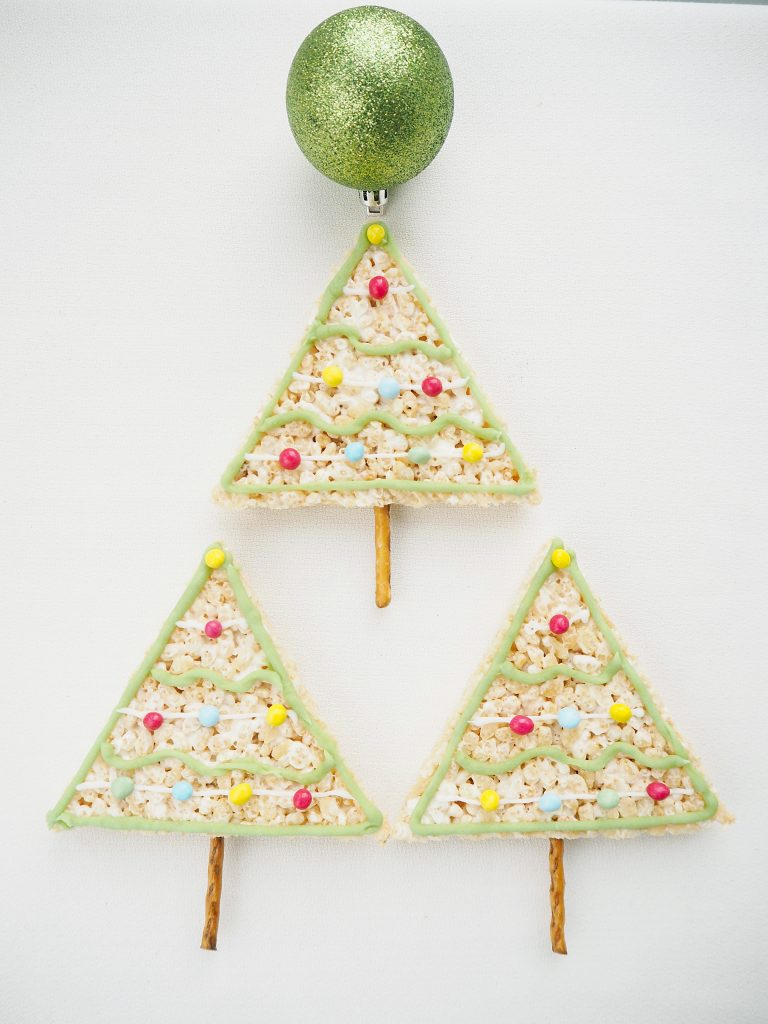 Rice Krispy Treats Christmas Trees with pretzel trunks lines up in a triangle shape like a Chirstmas tree