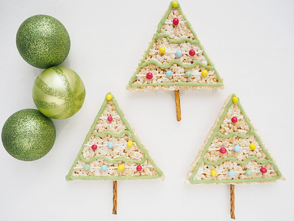 Rice Krispy Treats Christmas Trees with pretzel trunks with 3 glittery green Christmas baubles