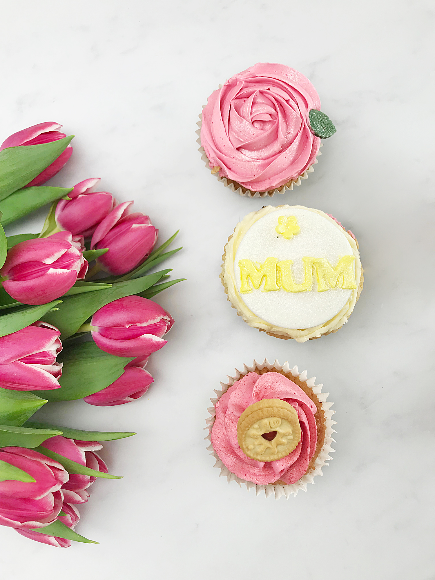 3 cupcakes with a bouquet of tulips. One of the cupcakes has Mum written on it, the other 2 are pink