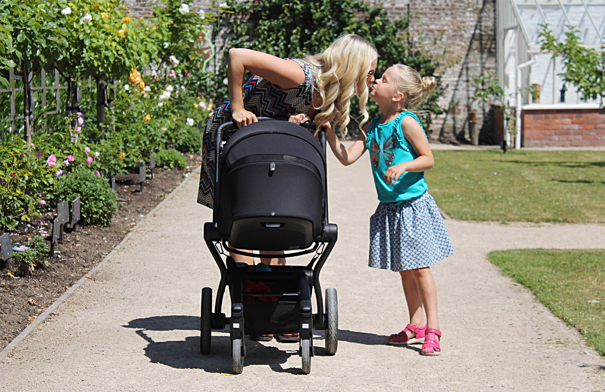 A woman bending down to give her daughter a kiss while pushing a black Joolz Hub travel system