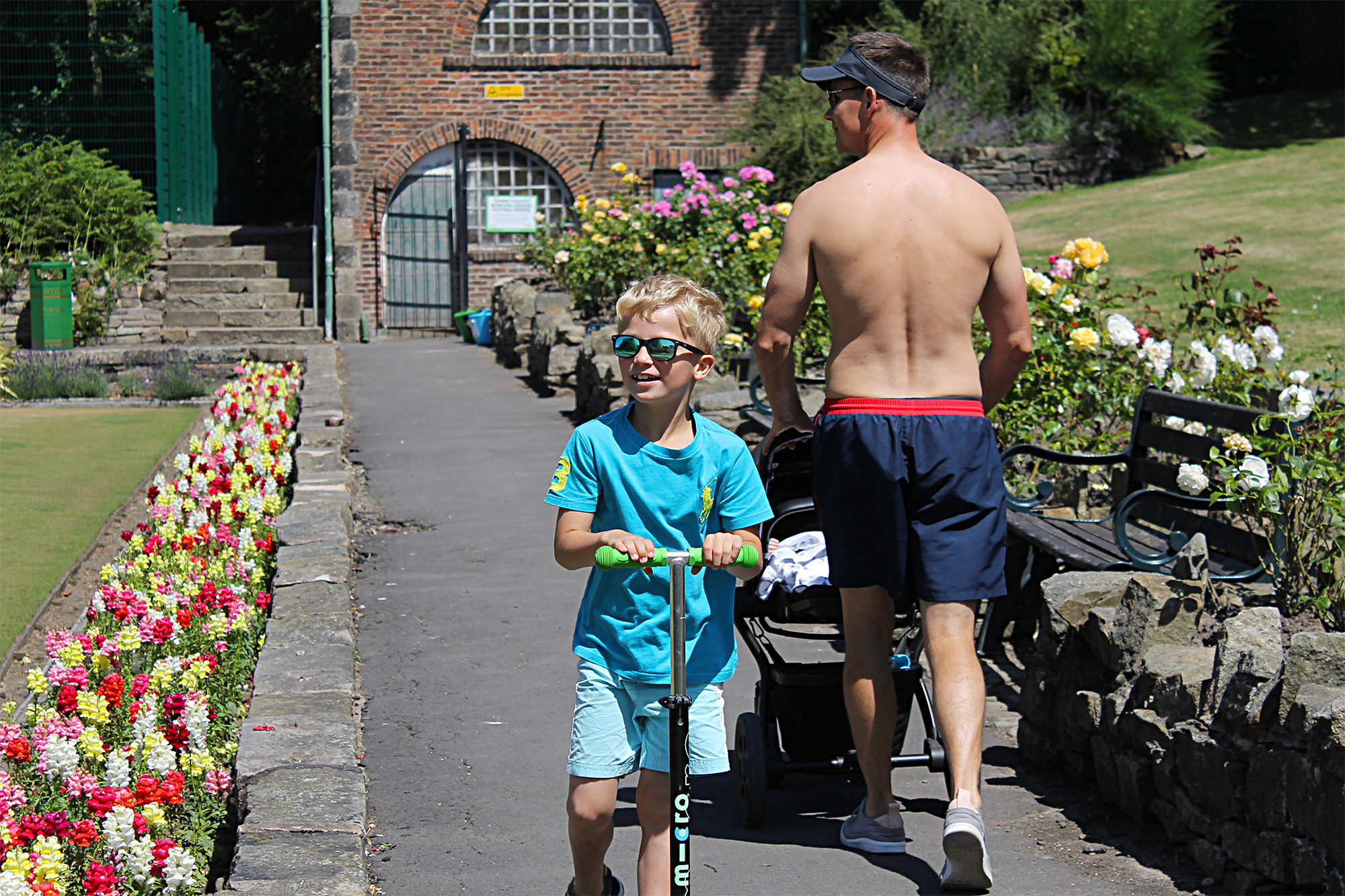 A boy scoots towards the camera, in a park, while a topless man walks away from it pushing a stroller