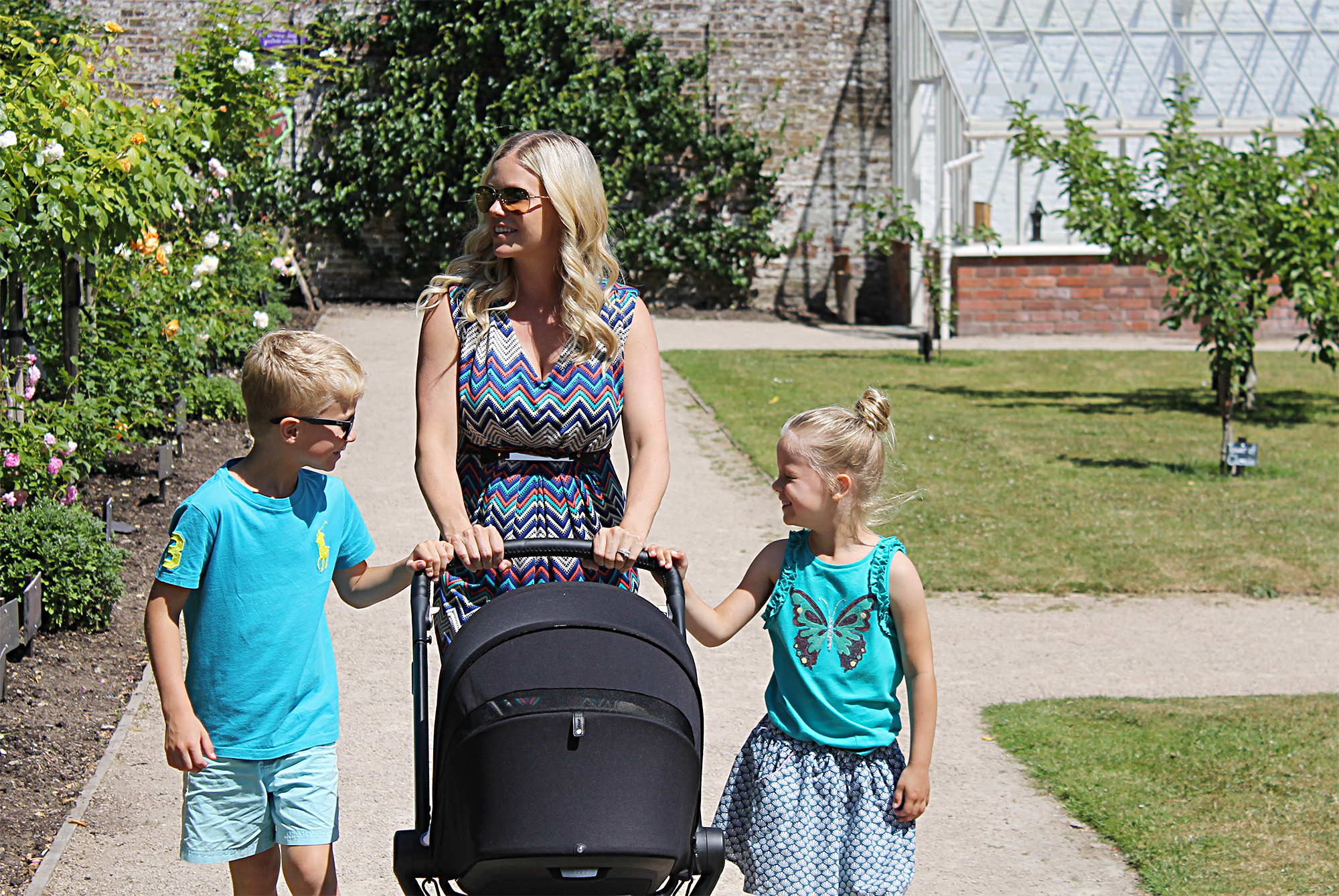 A woman wearing a patterned dress is walking in a park with 2 children walking beside her and pushing a black pram