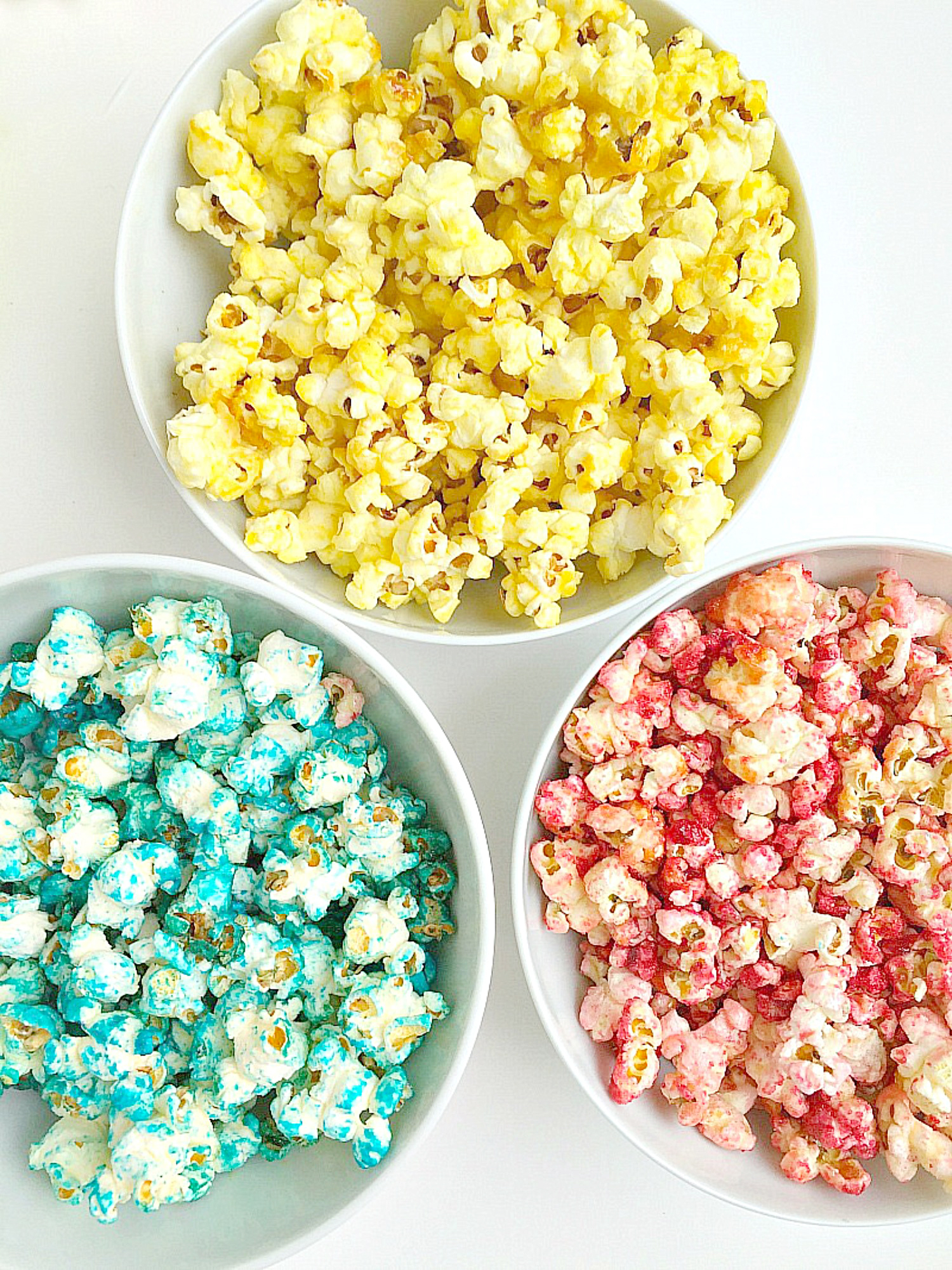 3 white bowls filled with a different colour of popcorn,