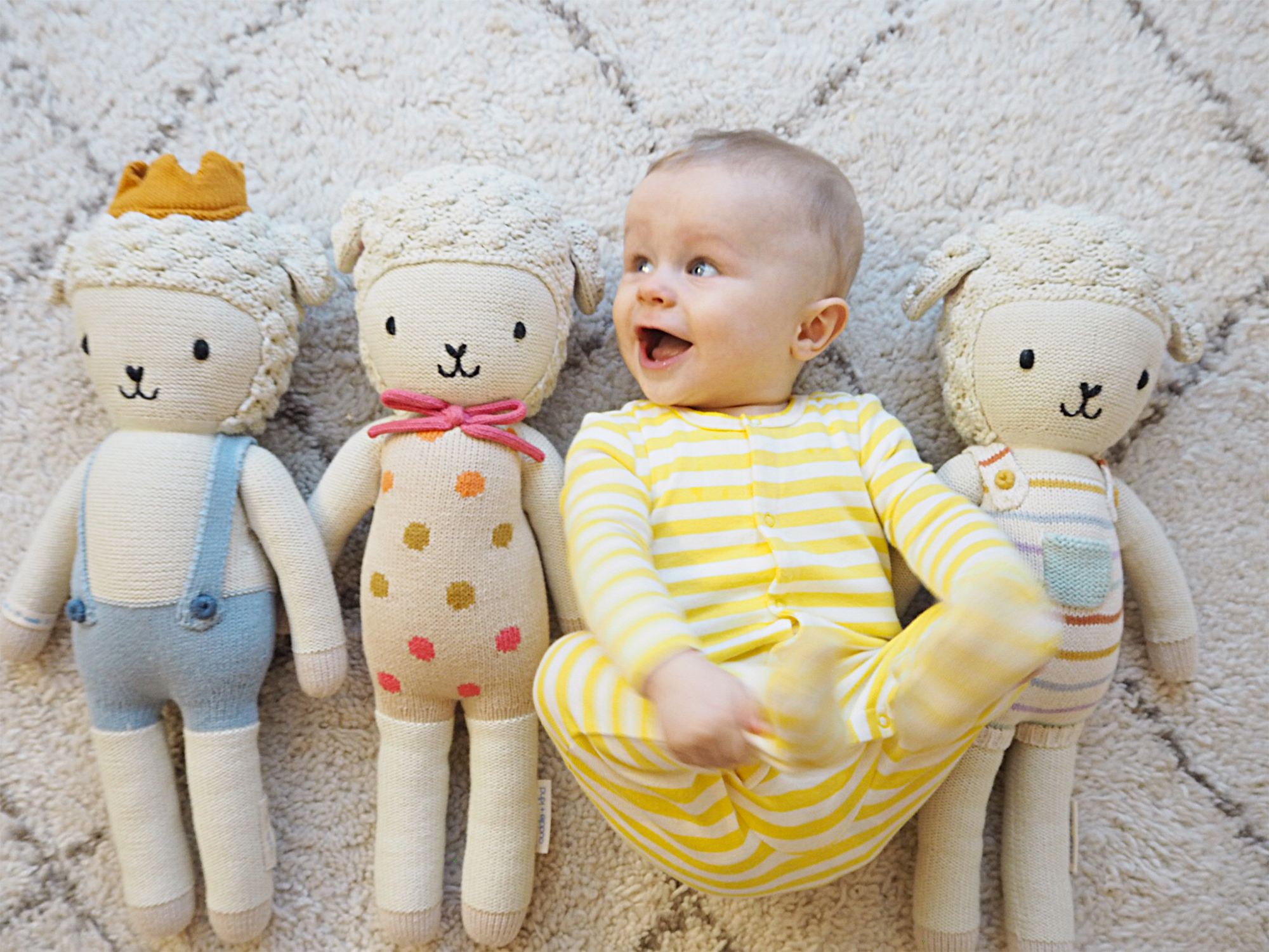 A baby wears a yellow and white sleep suit, lying on a rub with 3 sheep dolls next to him
