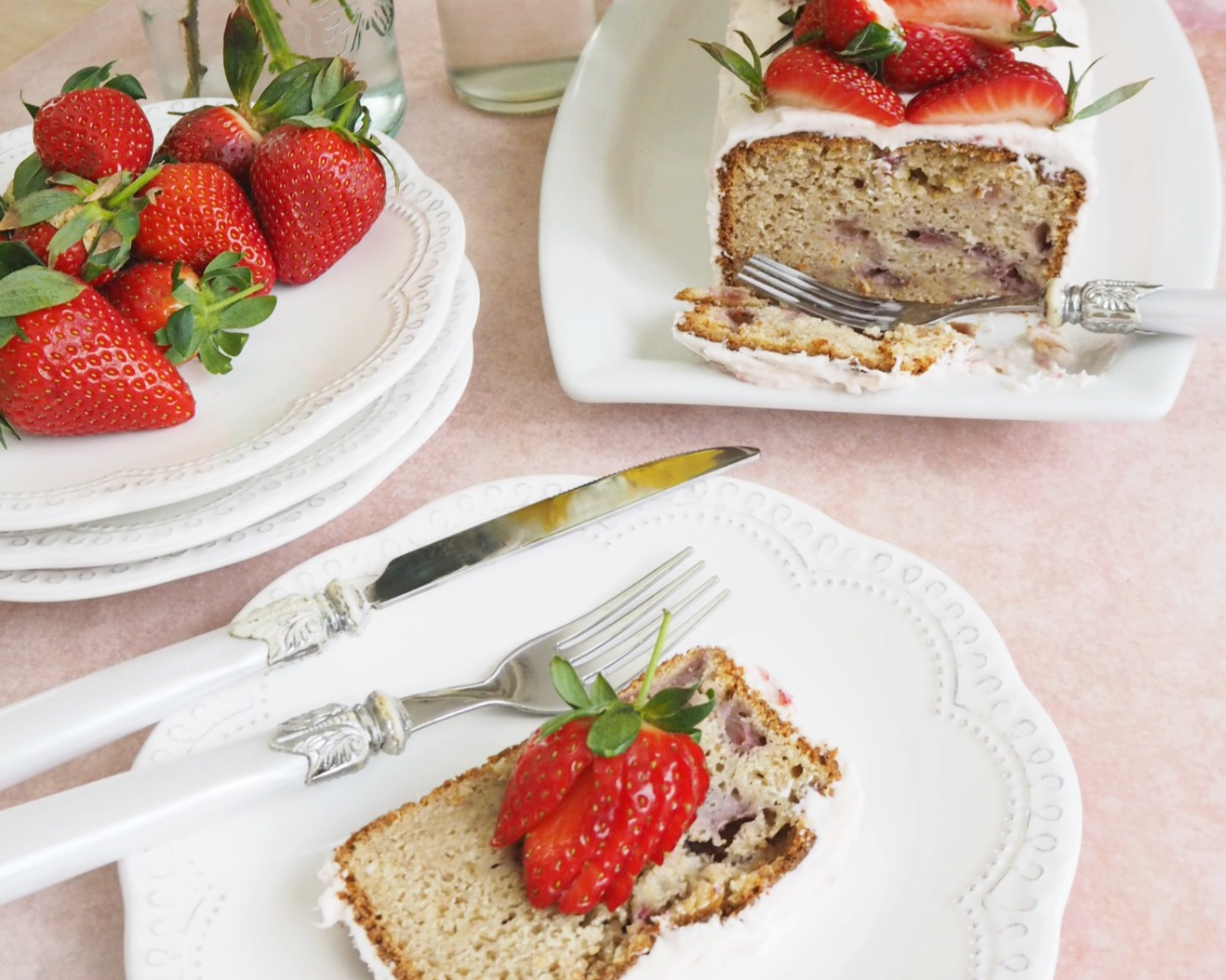 Strawberry bread with cream cheese frosting and fresh strawberries on top, sliced to show the inside of the loaf. A slice is on a plate to the right of the bread, and another plate has additional strawberries