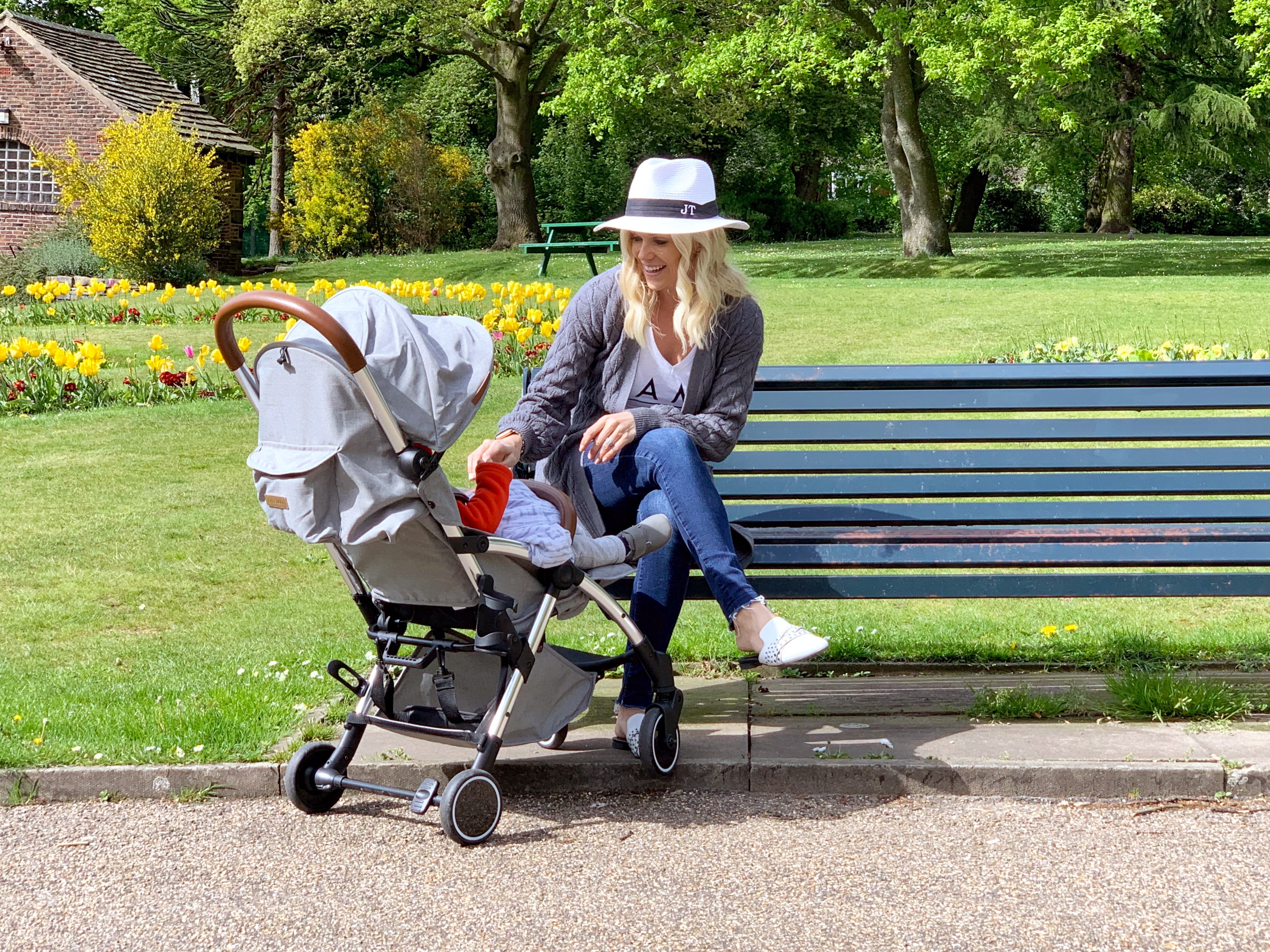 A woman sat on a park bench speaking to her child which is sat in a grey compact stroller.