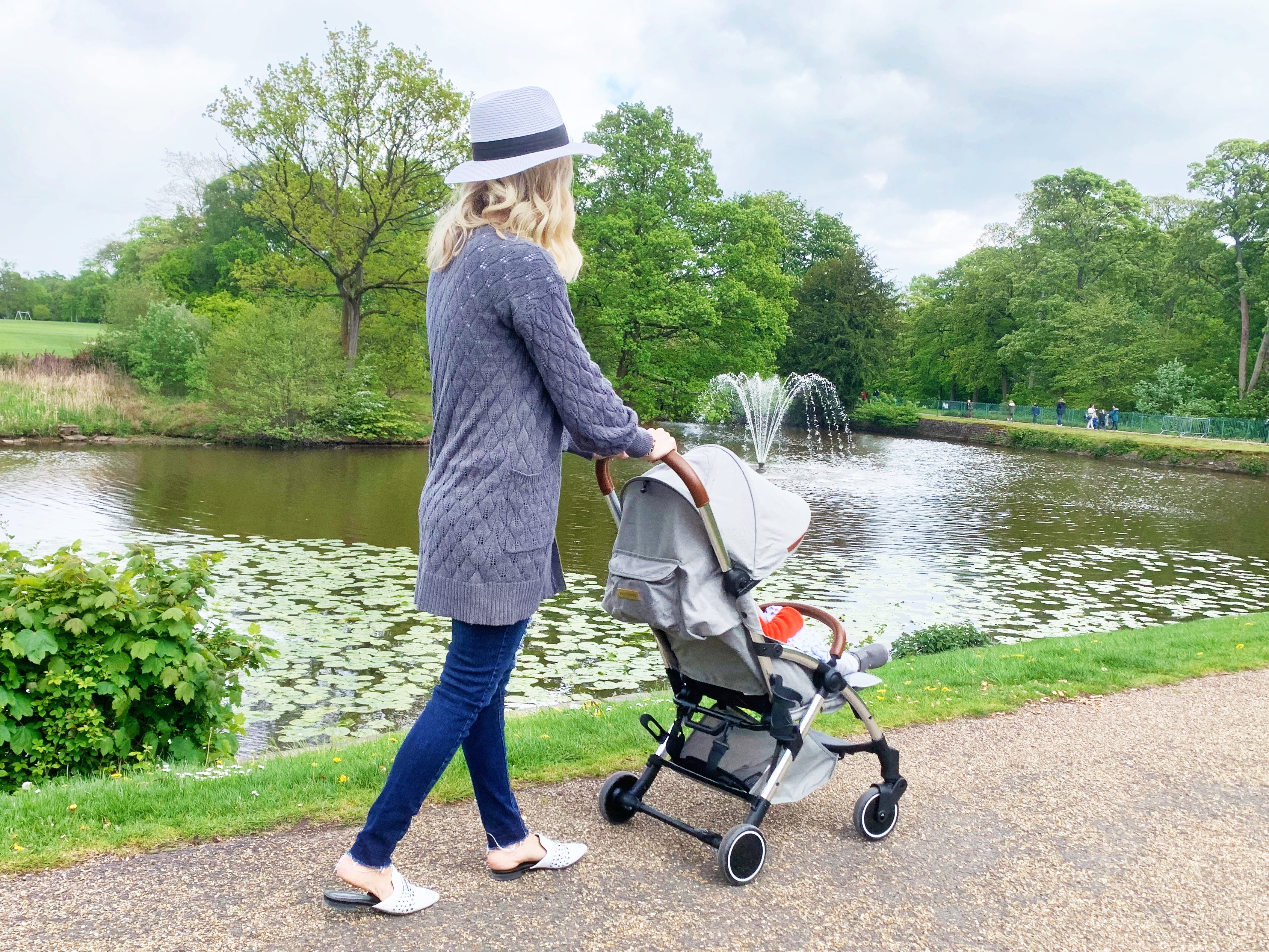 A woman is walking away from the camera pushing a stroller. She is wearing a grey cardigan and jeans and a white hat. She is walking next to a lake with a fountain in a park.