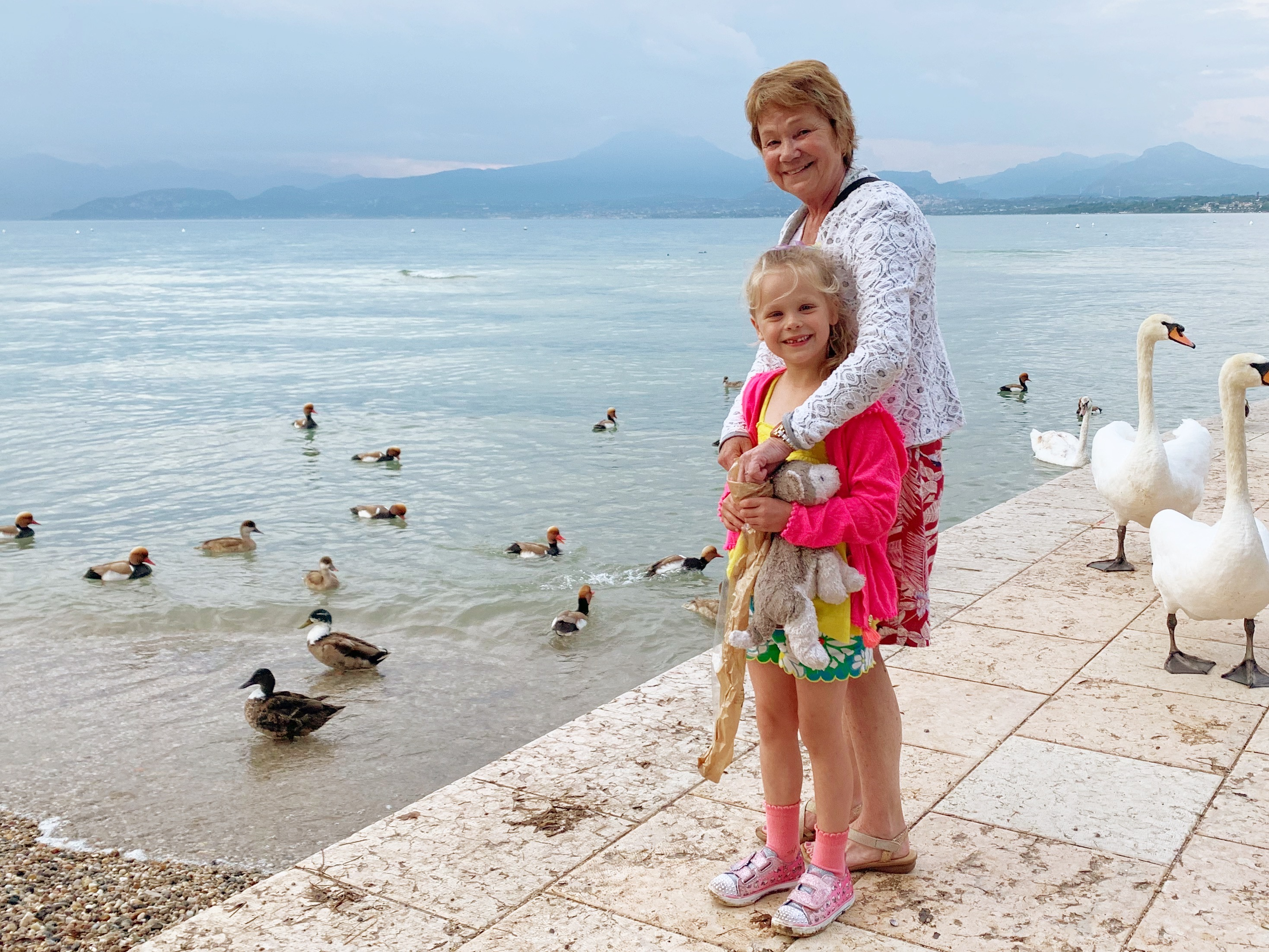 A grandmother and her granddaughter stand next to a lake surrounded by ducks and swans
