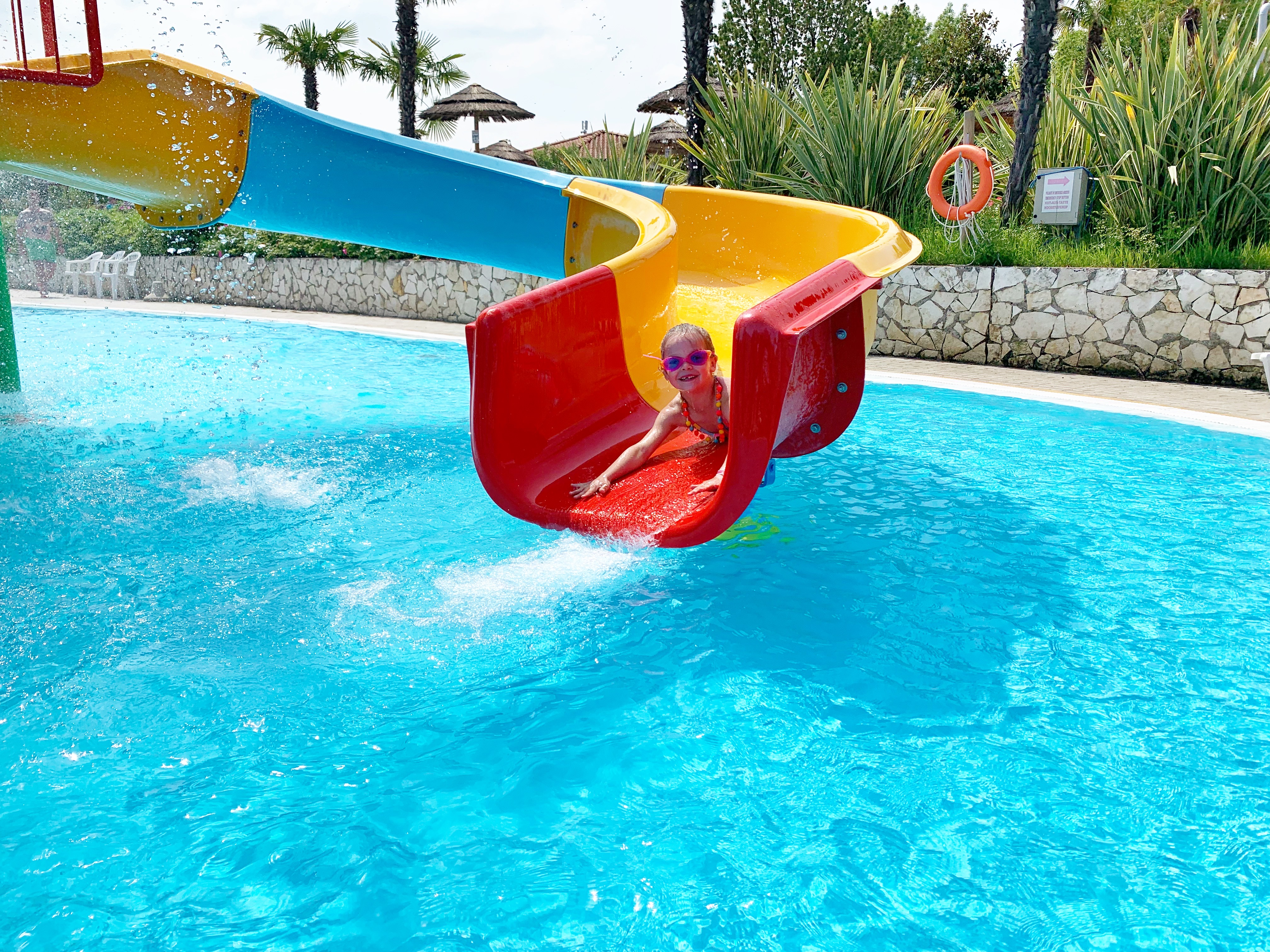 A girl comes down a multicoloured waterslide head first