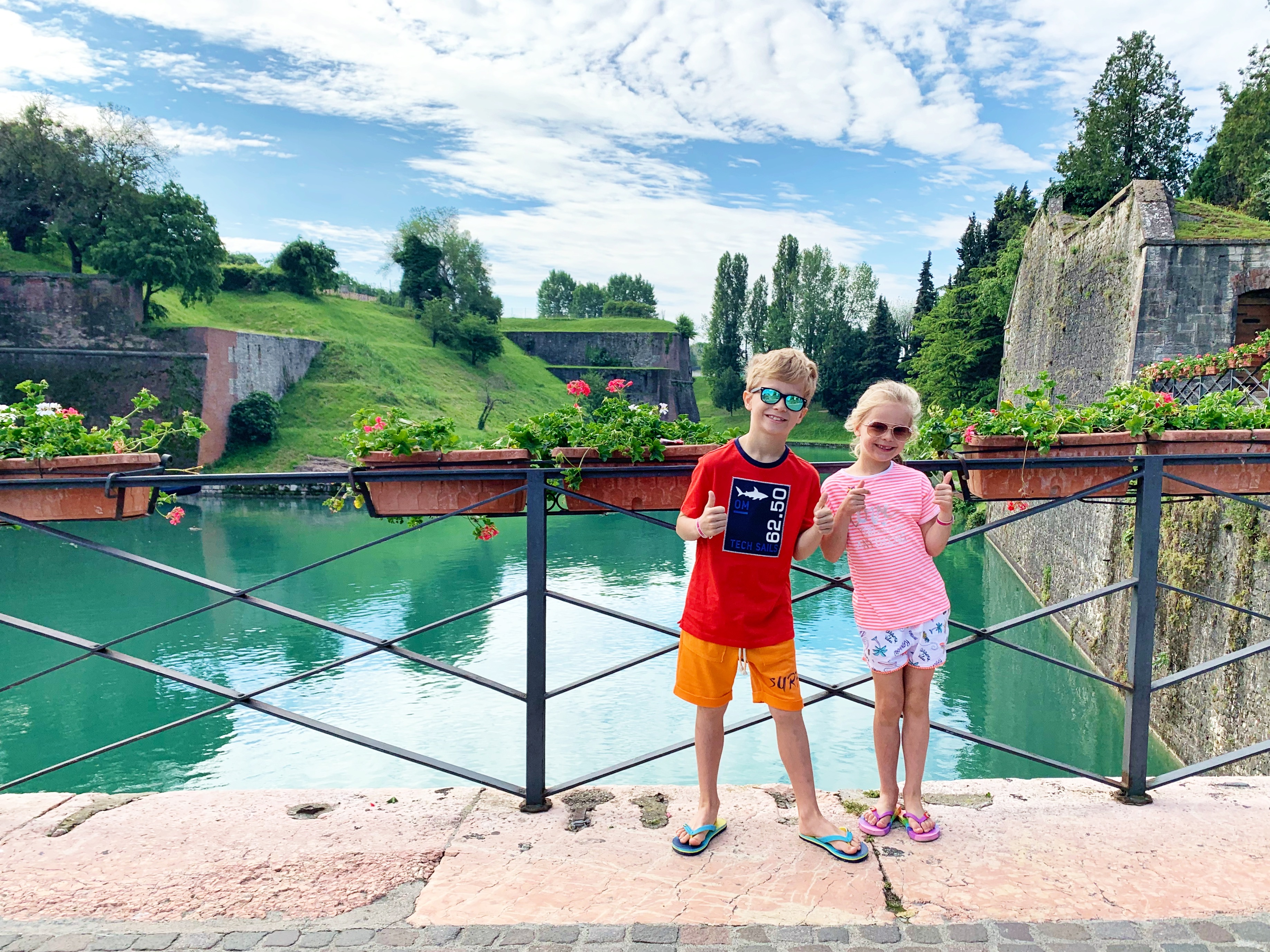 2 kids give a double thumbs up to the camera while standing next to some water in Italy
