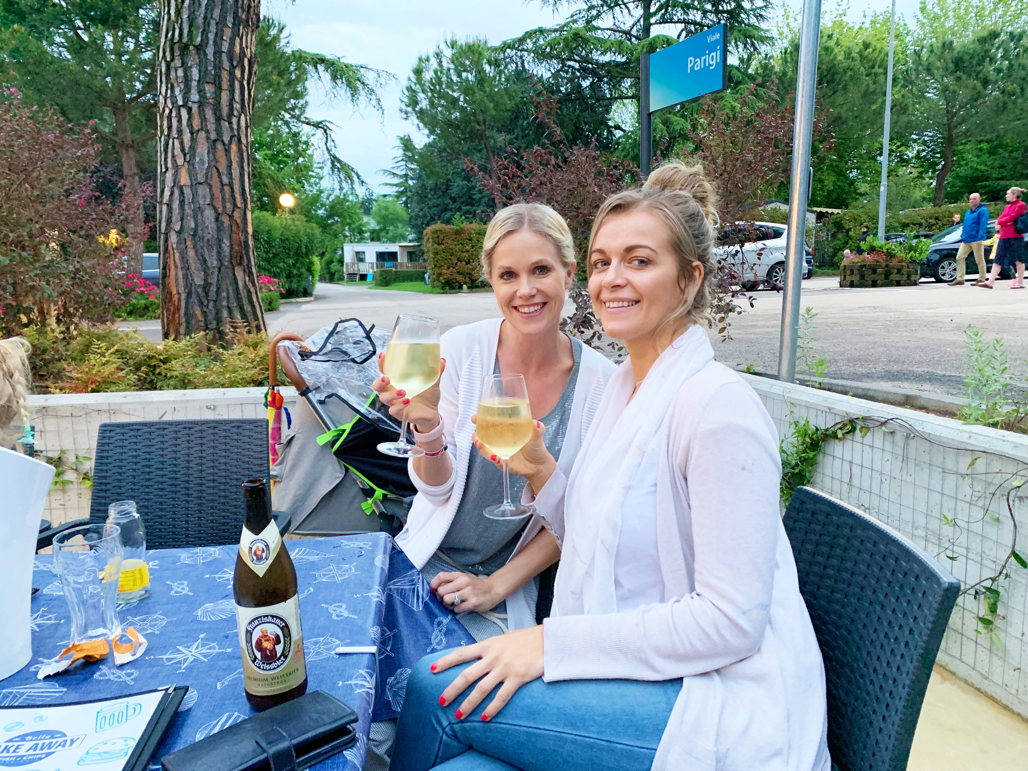 Two friends having a glass of wine in an outdoor restaurant
