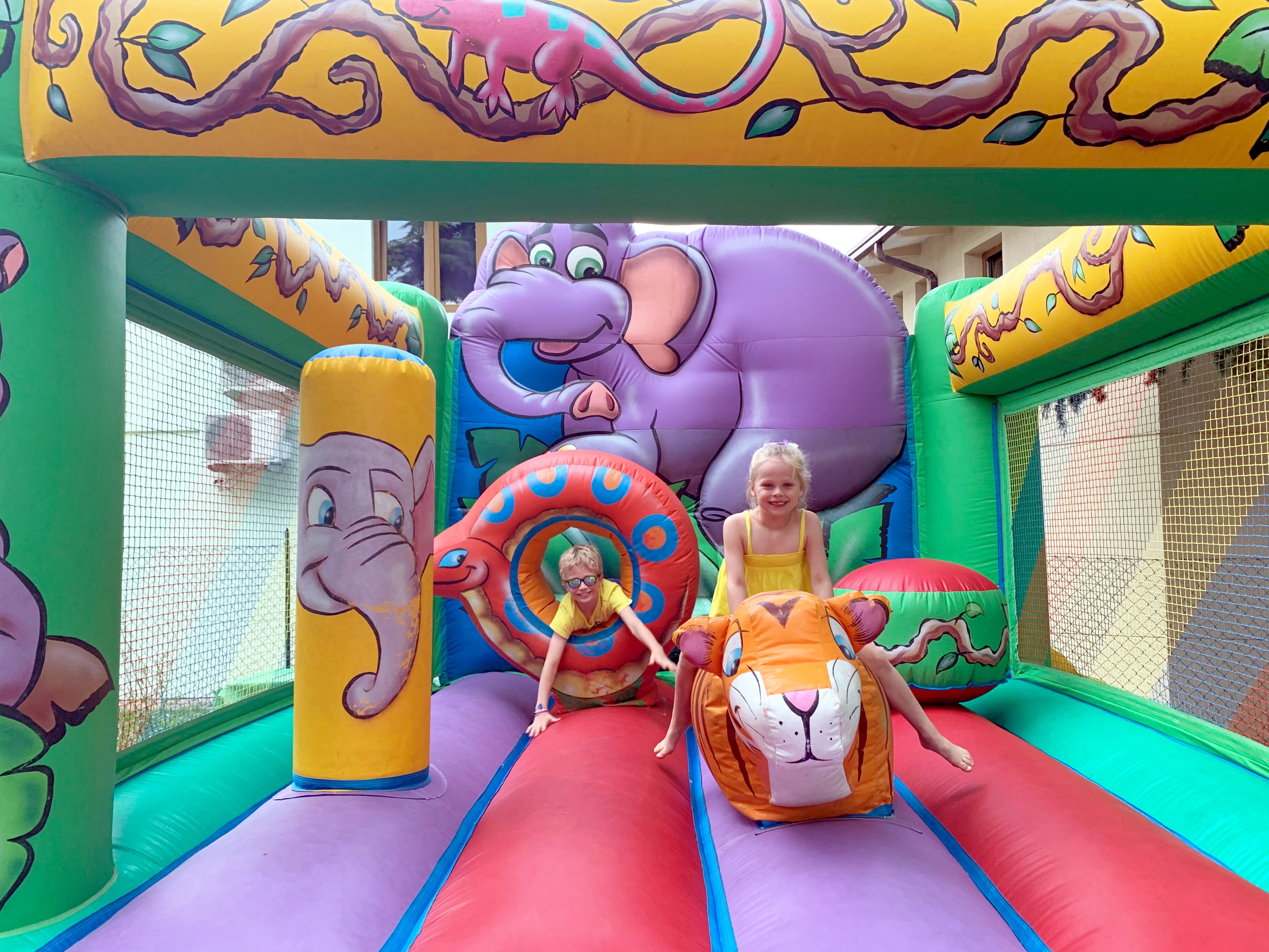 2 children playing on a bouncy castle with a jungle and elephant theme