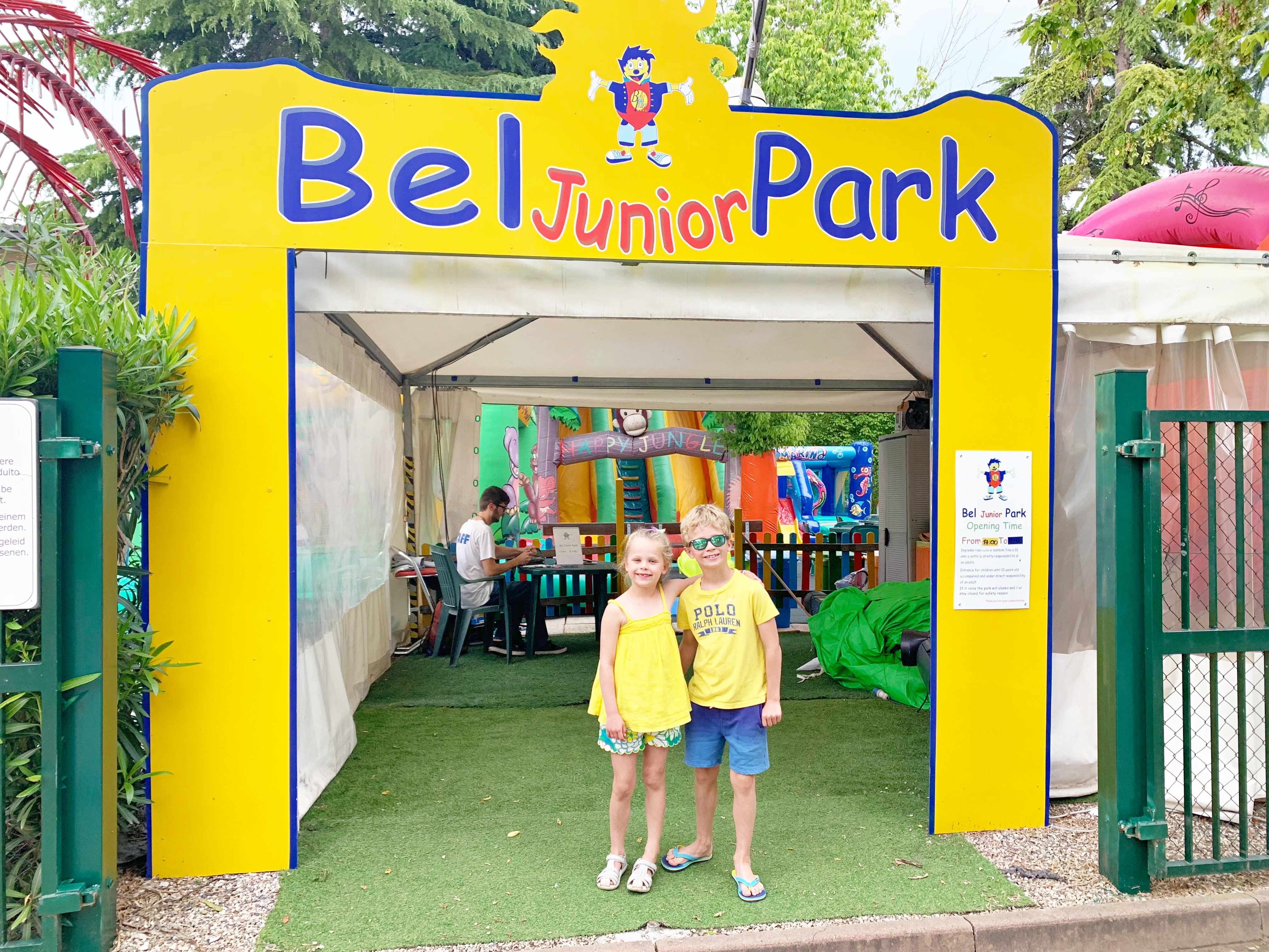"2 children in yellow shirts stand under a yellow sign that says ""Bel Junior Park"""