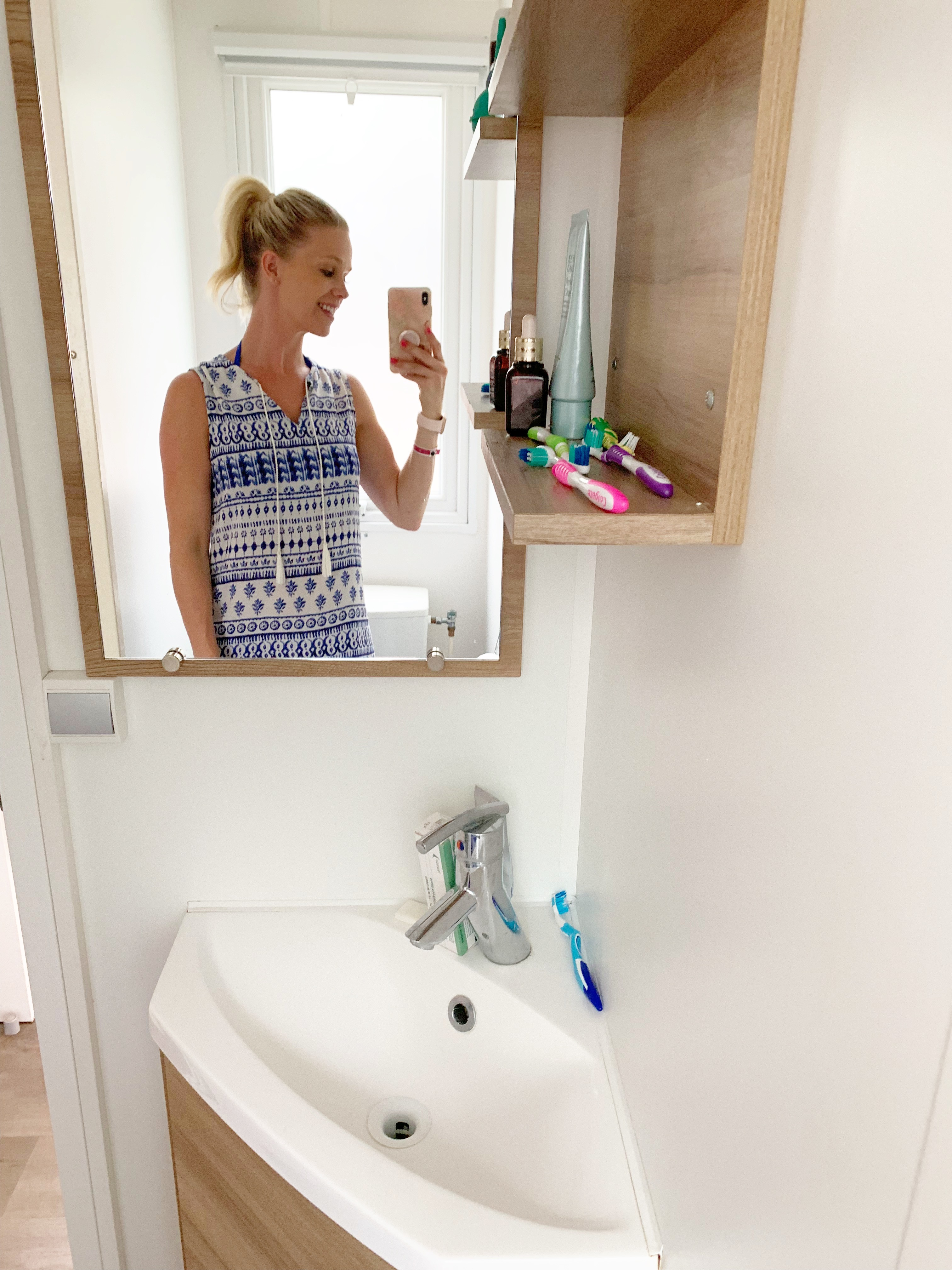 A woman smiling in the mirror on a bathroom wall. Below the mirror is a small sink with a toothbrush on it, and beside the mirror is a shelf with more toothbrushes and some other toiletries