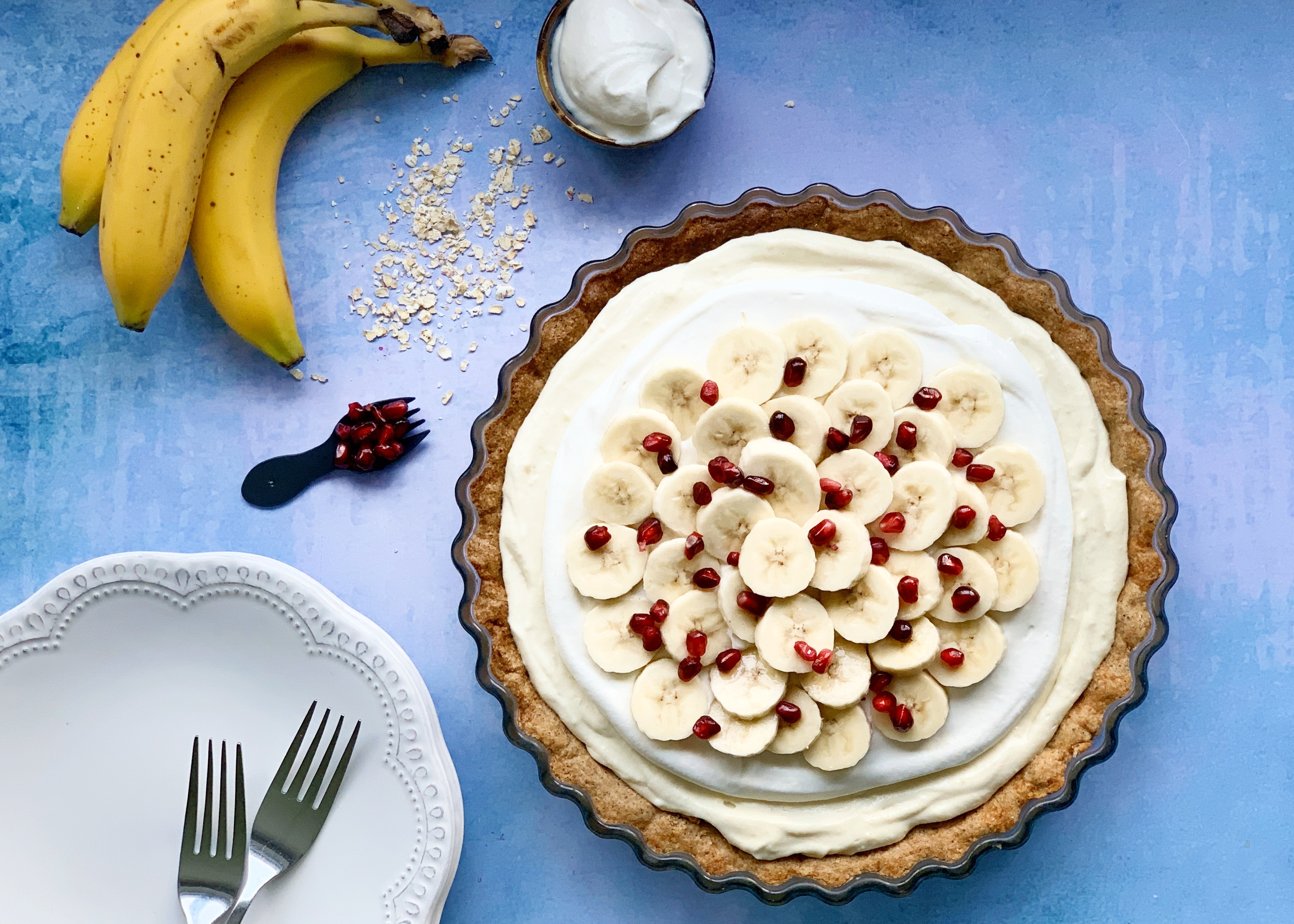 Vegan Banana Cream Pie with Pomegranate next to a plate with 2 forks on it, a bunch of bananas, some oats, cream and extra pomegranate. They are all sitting on a blue background.