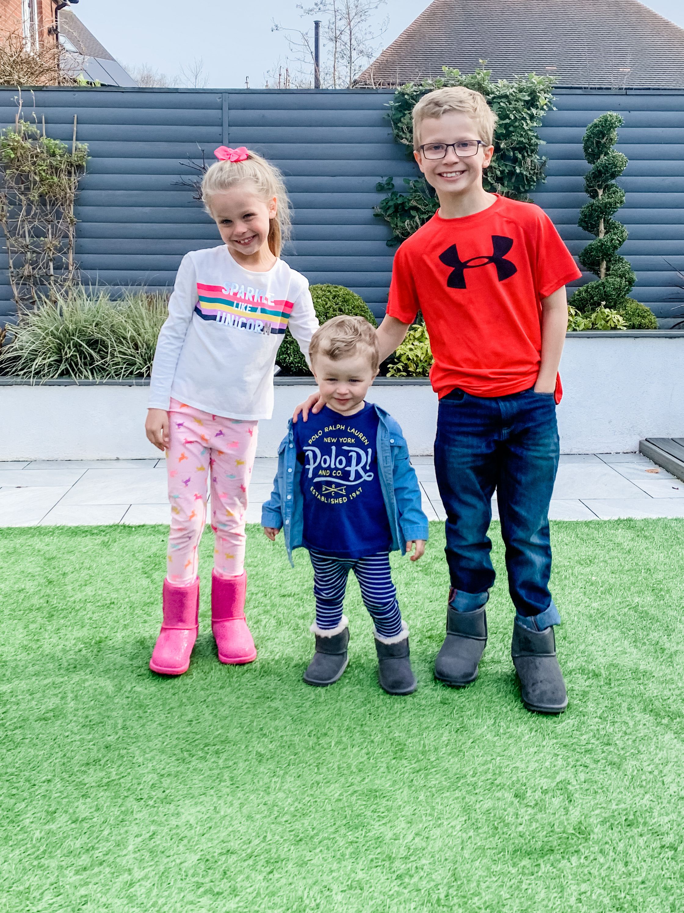 3 children standing in the garden smiling for the camera and wearing matching boots