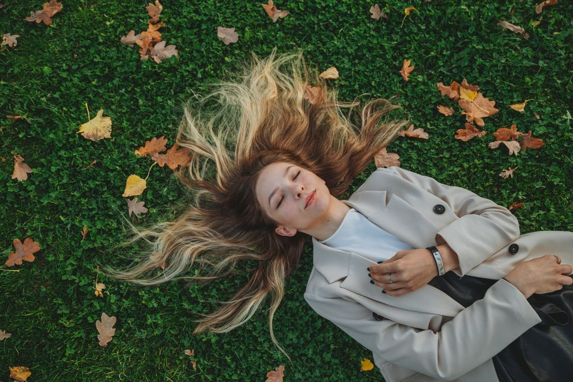 Young woman lying on grass in fall garden