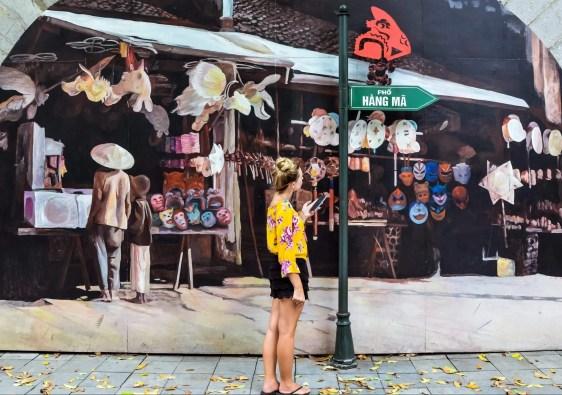 a girl with a yellow shirt is enjoying the street murals in Hanoi, Vietnam