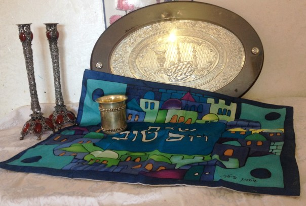 "And also our nicest things. A majority of stuff categorized as ""Judaica"" is for use on Shabbat. Pictured here are a pair of candlesticks (with the blessing for the candles inscribed on the shaft), a board for slicing the challah, our kiddush cup, and one of our prettiest challah covers (cloths used to cover the challah while kiddush is being made)."