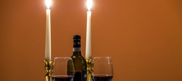 photo of two candles, two glasses of wine and a bottle of wine