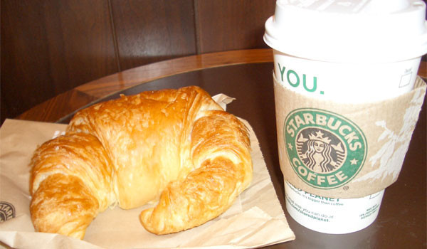 Cup of Starbucks coffee and butter croissant