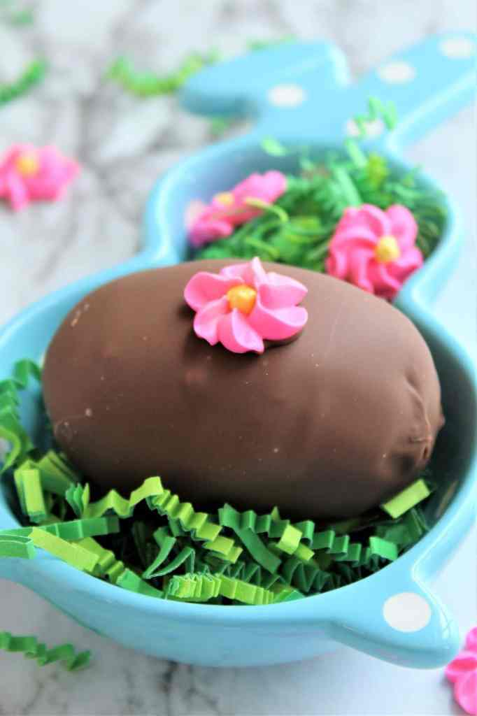 chocolate easter eggs in blue bunny dish with green easter grass
