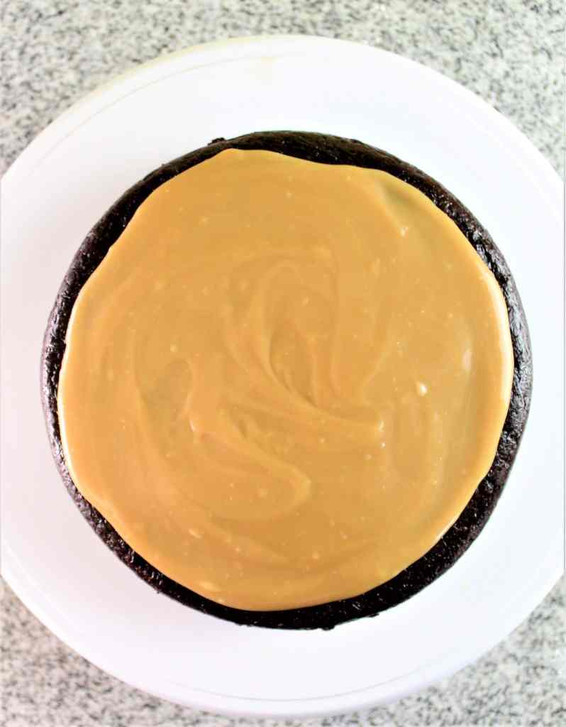 spreading caramel on top of a layer of chocolate cake