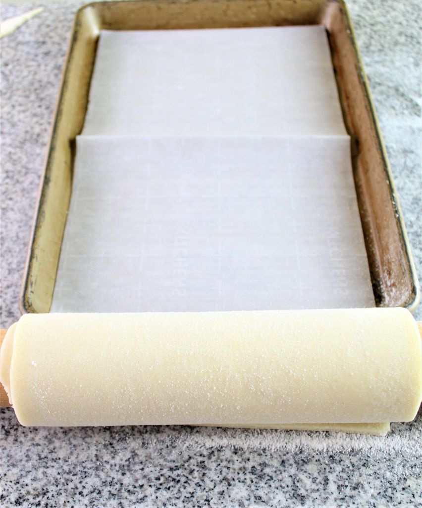 pastry rolled on rolling pin getting ready to unroll on pan