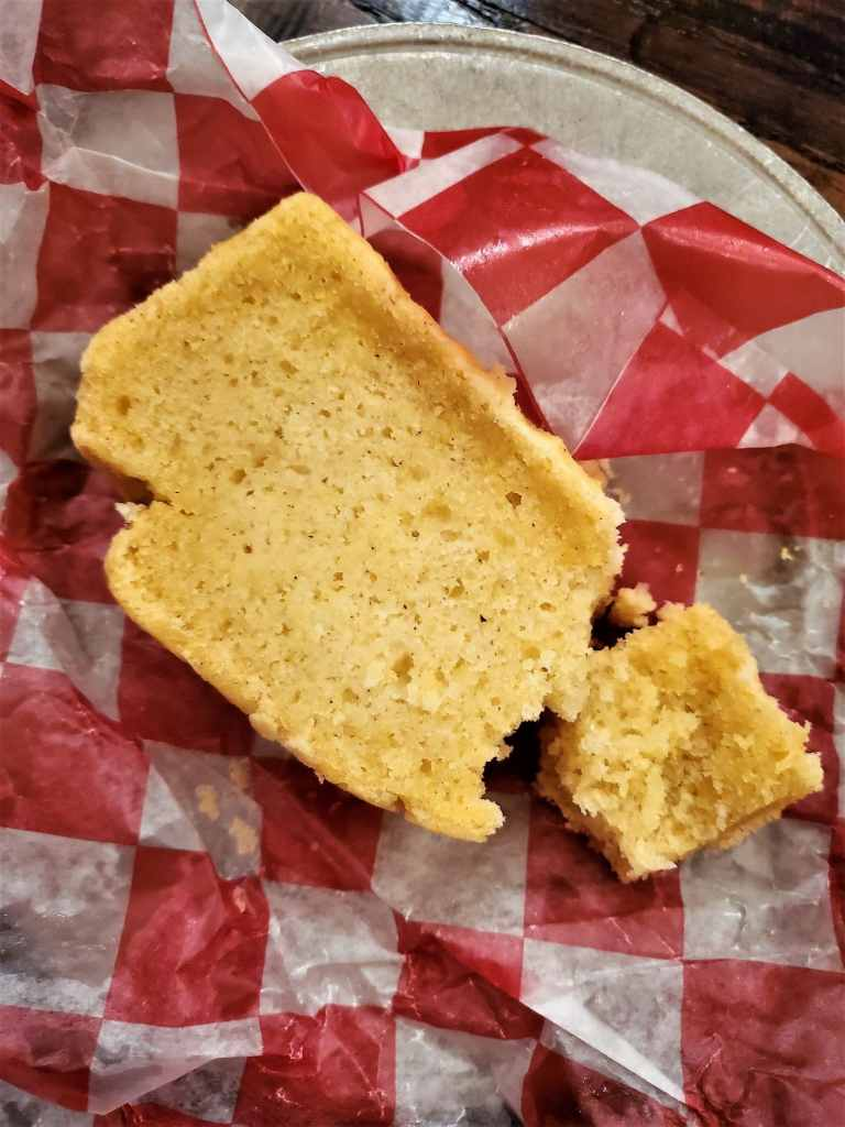 gluten free cornbread in red checked parchment paper on silver plate